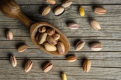 Top view Pistachio in nutshell in wooden shovel on wooden rustic backdrop. Peeling Pistachio in nutshell and shovel on wooden rustic backdrop, composition of royalty free stock photo