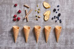 Top view of pistachios,banana slices,chocolate sticks,raspberries, blueberries falling in waffle cones on a grey background royalty free stock image