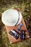 Top view of pithhelmet, camera, cellphone and. Top view of white pithhelmet, old camera, cellphone and sunglasses on retro suitcase Royalty Free Stock Photography