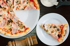 Top view of pizza slice on white plate over table. Top view of pizza slice on white plate over table stock images