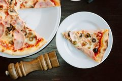 Top view of pizza slice on white plate over table. Top view of pizza slice on white plate over table royalty free stock photo