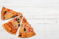 Top View of Pizza Slices with Tomato, Black Olives, Ham and Onio Stock Photo
