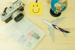 Top view. plane model, world model, passport, retro camera and p. Ost it note has smiley face all of this placed on wooden table. image for mock up, business Royalty Free Stock Images