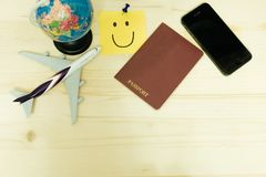 Top view. plane model, world model, passport, smart phone and po. St it note has smiley face all of this placed on wooden table. image for mock up, business Stock Photography