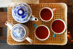 Top view on a plastic tray with two ceramic white-blue teapots and three cups with Thai tea. Top view on a plastic tray with two ceramic white-blue teapots and stock images