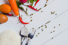 Top view of a plate of cooked rice. With some vegetable carrot, chili,tomato,and egg on the white  wooden table floor for background Stock Image