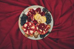 Top view of plate with different fruits. On red tablecloth stock photography