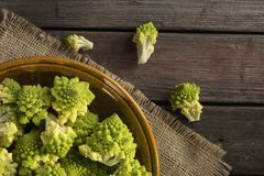 Romanesco broccoli. Top view of a plate filled with fresh romanesco broccoli placed on a rustic wooden table. Focus on the broccoli next to the plate Royalty Free Stock Photos