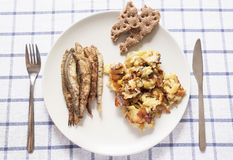 Top view of the plate of food consisting of fried fish, potatoes and crisp bread. And nearby lie knife and fork on tablecloth royalty free stock photos