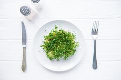 Top view plate with fresh organic sprout micro greens served with cutlery and herbs on the white wooden table. Healthy Raw diet fo. Od concept. Copy space for Royalty Free Stock Photo