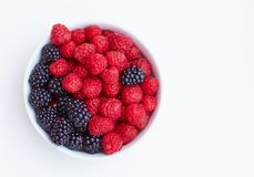 Top view on plate with fresh and ripe raspberries and blackberries on white Stock Photography