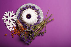 Top view of a plate with a ring cake, a candle, almond, cinnamon, snowflakes, twigs of flowers on a violet background. Top view of snowflakes, almond, sticks of Royalty Free Stock Image