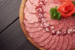 Top view of plate of sliced sausage decorated with aromatic herbs. Sausage on wooden catering platter, flat lay of meat royalty free stock image