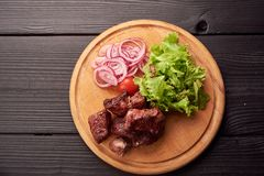Top view of plate of sliced sausage decorated with aromatic herbs. Sausage on wooden catering platter, flat lay of meat royalty free stock photo