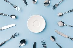 Top view of plate surrounded by flatware. Isolated on blue stock photo