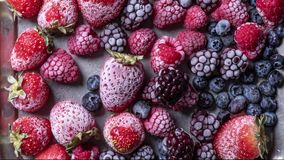 Top view plate with variety of forest fruits, berries and hearts on a blue background. Top view of a plate with variety of forest fruits, berries and hearts on a stock video footage