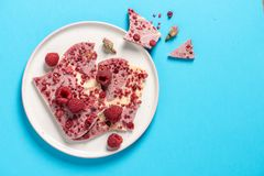 Top view of a plate white and pink chocоlate, raspberries, rose royalty free stock photo