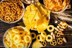 Top view of plates with snacks near wheat, scattered nuts and pr. Etzels on dark wooden desk. Food and beverages concept Royalty Free Stock Images