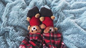 Top of view of playing feet at home in bed dressed socks with cute teddy bears and in pajamas. slow motion. 3840x2160. Playing foot at home in bed dressed socks stock footage