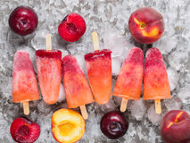 Top view of plum and peach popsicle on gray metal background. Fruit popsicles ice cream with fresh plums and peach Stock Photography