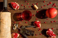 Top view pomegranate wine, bottle opener and fruit. Top view fresh ripe pomegranate fruit, bottle and glass with wine, cork and bottle opener Royalty Free Stock Photography