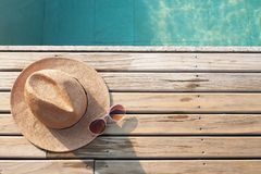 Top view of poolside, sun hat and sunglasses on wooden floor. Travel vacation stock photography