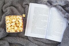 Top view of popcorn box and open book on warm blanket