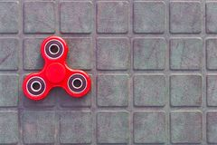Top view of the popular red spinner gadget in 2017 on the blue-green background.  stock photo