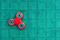 Top view of the popular red spinner gadget in 2017 on the blue-green background.  stock images