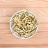 Dried oat tea. Top view of a porcelain bowl with dried oat on a wooden background Stock Photo