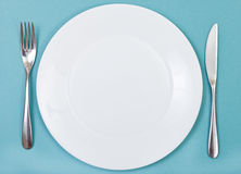 Top view of porcelain plate, fork, knife on green Stock Image