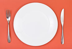 Top view of porcelain plate, fork, knife on red Stock Image
