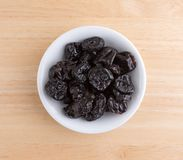 Dried bing cherries in a small white bowl. Top view of a portion of dried bing cherries in a small white bowl atop a wood table Royalty Free Stock Photo