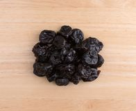 Dried bing cherries on a cutting board. Top view of a portion of dried bing cherries on a wood cutting board Royalty Free Stock Photo