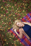 TOP VIEW: Portrait of a beautiful young woman lies on a plaid in park in the fall Stock Images