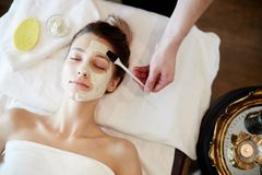 Beautifying Skincare in SPA. Top view portrait of beautiful young women enjoying SPA, lying on massage table with cosmetologist applying face mask to her face Royalty Free Stock Photography