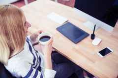 Top view portrait of a girl drinking coffee in office Royalty Free Stock Photography
