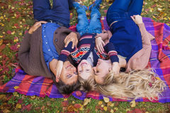 TOP VIEW: Portrait of a happy young family on a plaid in park in the autumn Royalty Free Stock Photography