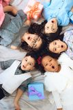 Top view. Portrait of joyful children who lie on floor in shape of circle. Royalty Free Stock Images