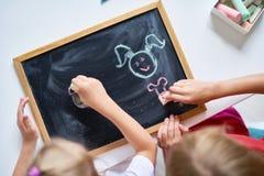 Little Girls Drawing on Chalkboard stock image