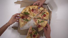 Top view portrait of people hands taking slices of pizza, group of friends sharing pizza together, colleagues ordered stock footage