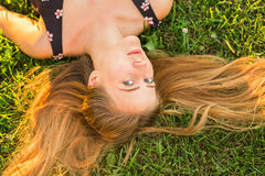 Top view portrait of a pretty young woman relaxing on a grass close-up royalty free stock photography