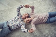 Old man and woman reposing on rug with joy Royalty Free Stock Image