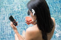 Sexy woman play smartphone at pool. Top view portrait of sexy Asian beautiful woman with swimsuit and sunglasses dirnk tomato juice and play social media via Stock Photography