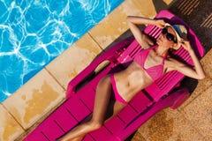 Woman sunbathing on sun bed by swimming pool. Top view portrait of woman in pink bikini sunbathing on sun bed by the swimming pool royalty free stock photos