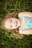 Top view portrait of a smiling shy little girl. Lying on green grass stock photos
