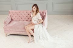 Beautiful young pregnant woman in white dress peignoir sitting on pink sofa, showing her naked belly, looking at camera royalty free stock image