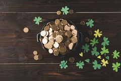 Top view of pot with golden coins and shamrock on wooden table Stock Image