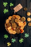 Top view of pot with golden coins and shamrock on wooden table, st patricks day concept stock photography