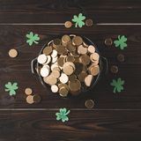 Top view of pot with golden coins and shamrock on wooden table Royalty Free Stock Images